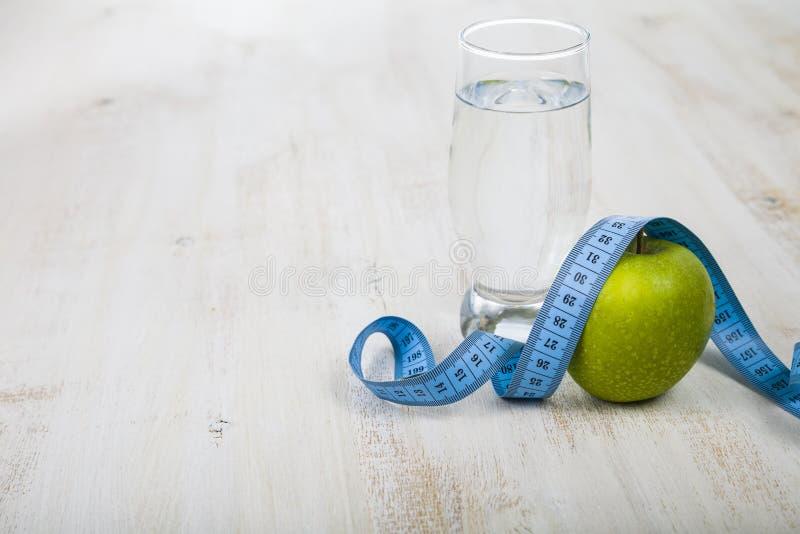 绿色苹果、杯水和在一张木桌上的测量的磁带 图库摄影