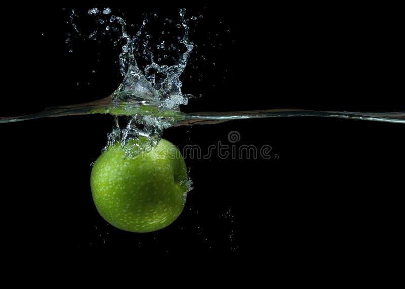 绿色苹果在与飞溅的水中 免版税库存图片