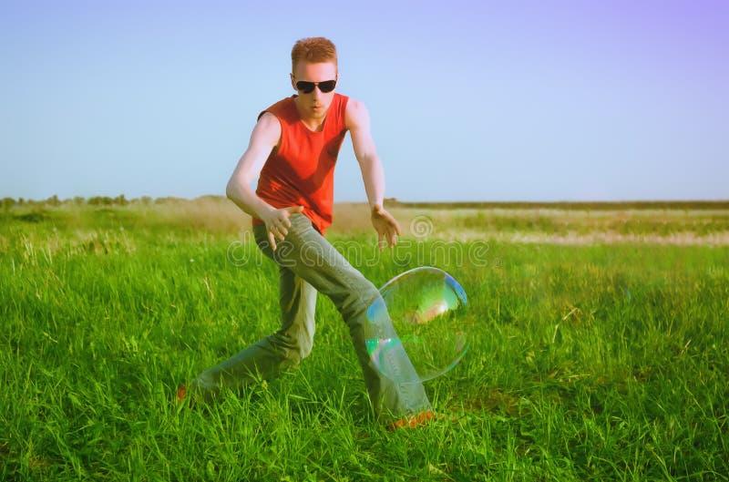 绿色草甸的年轻人 免版税图库摄影
