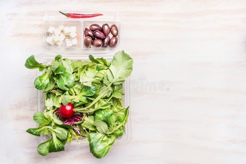 绿色菜色拉盘用橄榄和希腊白软干酪在白色木背景,顶视图,拷贝空间 健康吃,节食 免版税库存图片