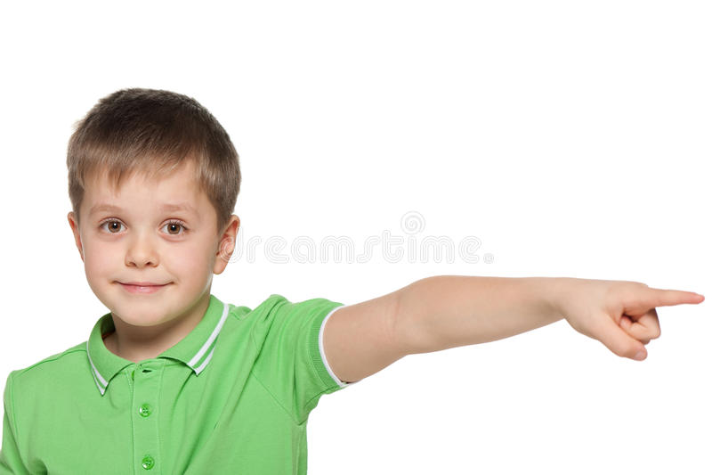 绿色衬衣的男孩显示她的手指对边 库存图片