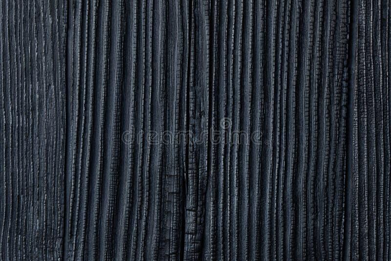 黑色被烧的&被烧焦的木头、雪松或者杉木议院支持的Backgrou 免版税库存照片
