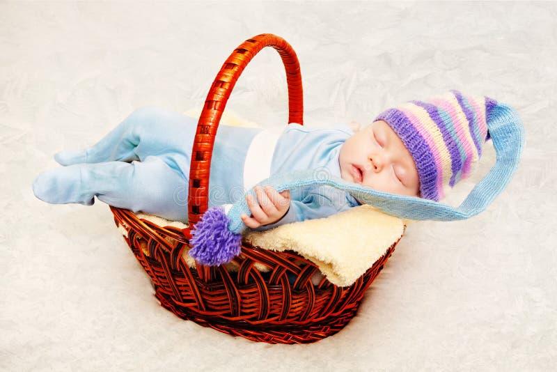 紫色被编织的盖帽的一个新出生的婴孩 图库摄影