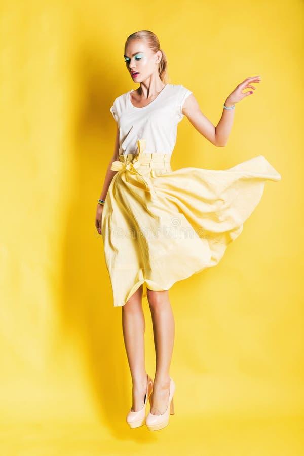 黄色裙子的跳跃的白肤金发的妇女 免版税库存图片