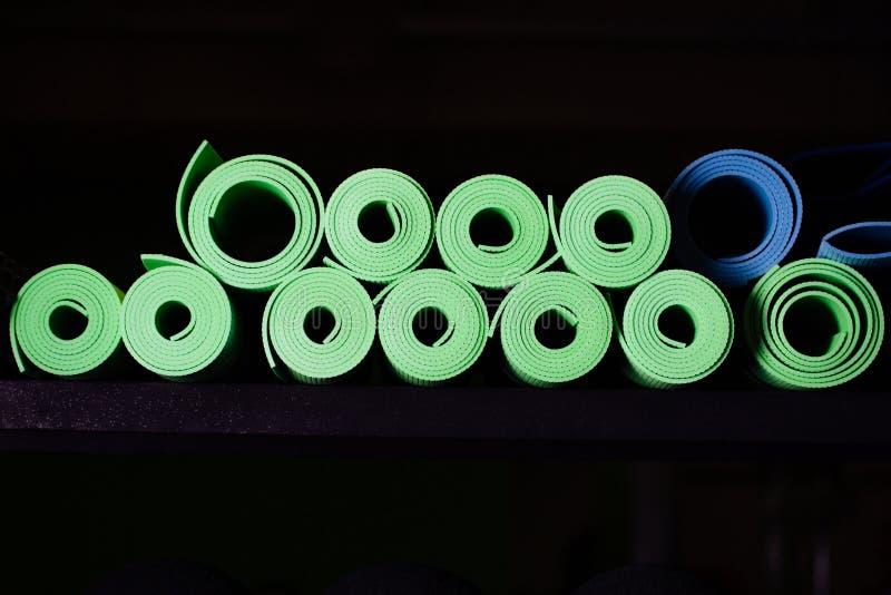 绿色许多瑜伽的席子和蓝色颜色 库存图片
