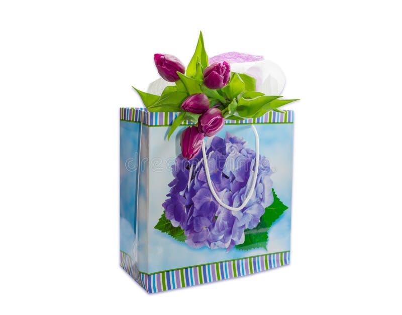 紫色郁金香花束在一个纸袋的与礼物 库存照片