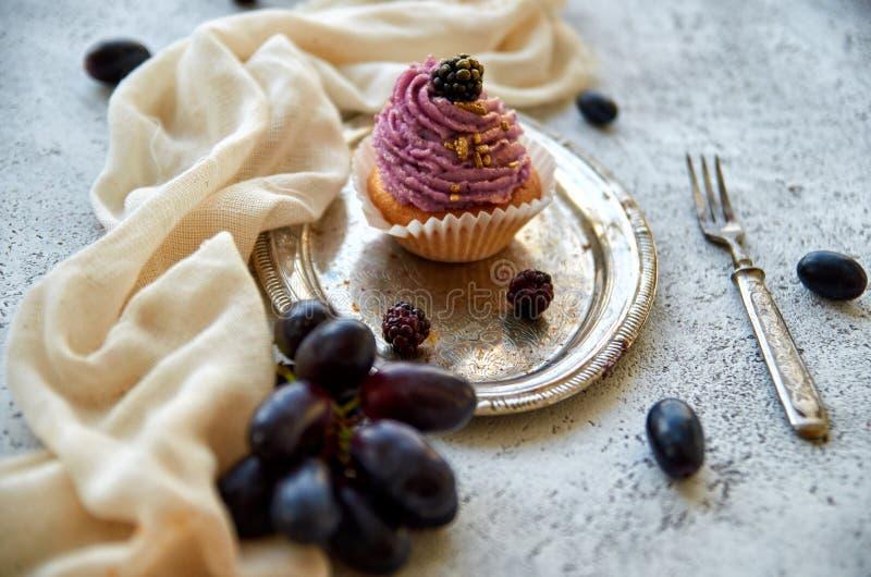 紫色金黄杯形蛋糕用在用长的匙子装饰的银色葡萄酒盘子的黑莓,浅褐色的布料,新鲜的蓝色葡萄 图库摄影