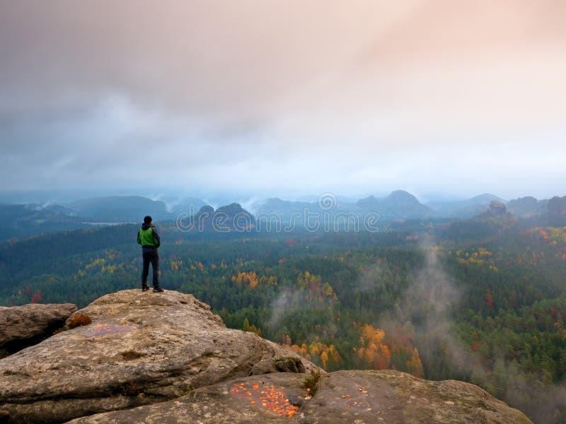 绿色防风衣的远足者,盖帽和黑暗的迁徙的长裤在山峰岩石站立 库存图片
