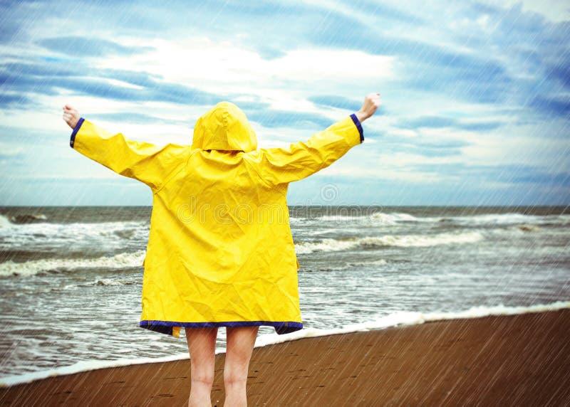 黄色雨衣的少妇 免版税图库摄影