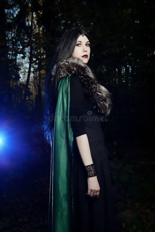 绿色雨衣的,作为巫婆的神色年轻美丽的女孩在万圣夜在黑暗的森林里 库存照片