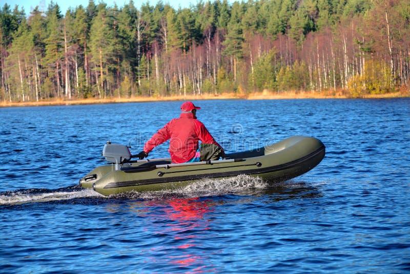 绿色,快速汽艇,有马达的可膨胀的橡皮艇在木湖 免版税库存图片