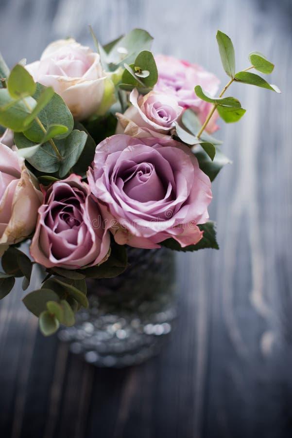 紫色,淡紫色在花瓶的颜色新鲜的夏天玫瑰有黑片剂的 免版税库存图片