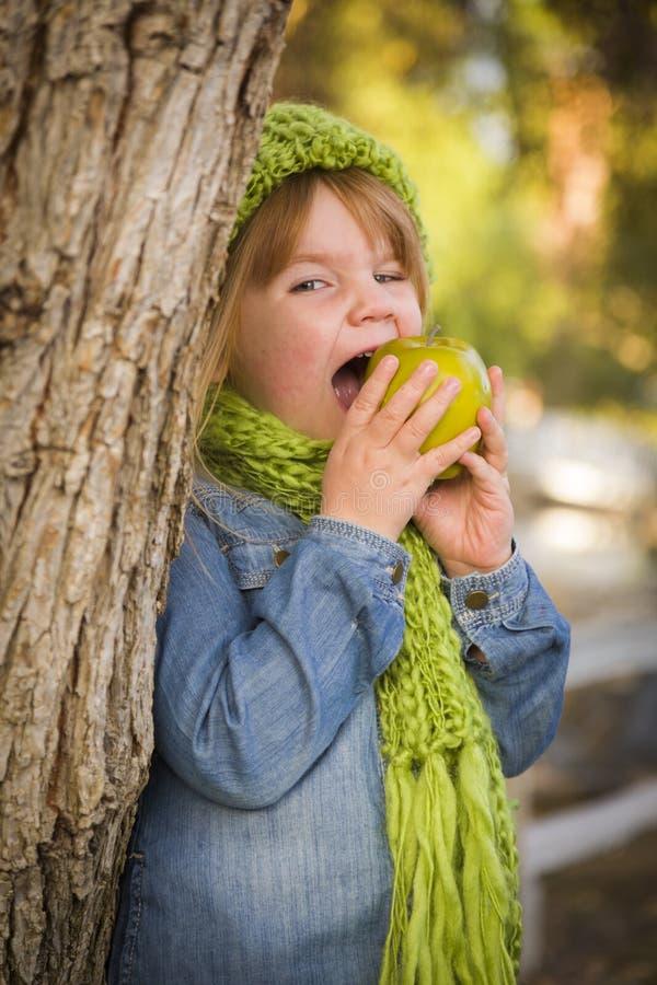 戴绿色围巾和帽子的女孩吃苹果计算机外面 库存图片