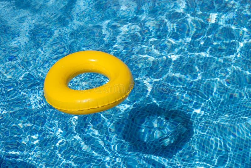 黄色水池浮游物,在凉快的蓝色refreshi的水池圆环 免版税库存照片