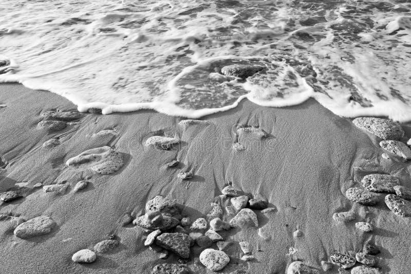 黑色&海的白的波浪海滩的与沙子和石头 免版税库存图片