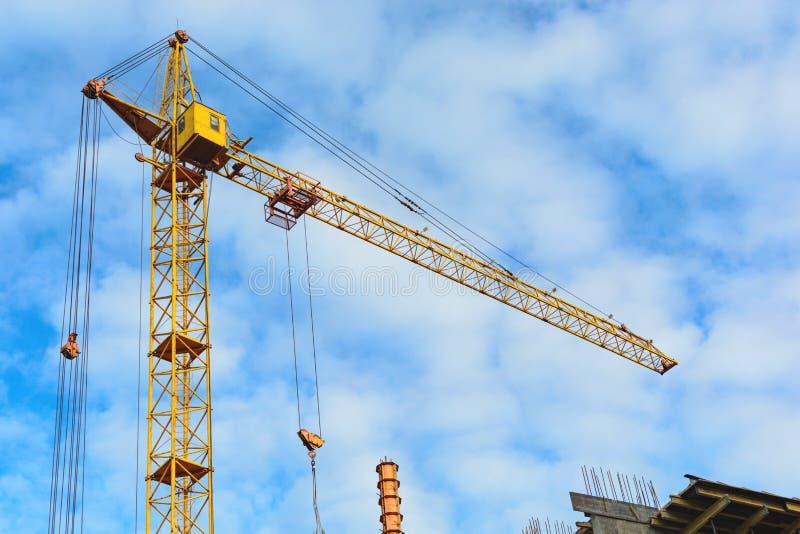 黄色建筑用起重机和未完成的大厦与金属具体结构在蓝天背景与白色 免版税图库摄影
