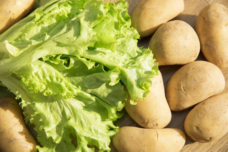 绿色莴苣叶子和土豆 在木背景的莴苣叶子 在厨房用桌上的新鲜的莴苣 库存图片