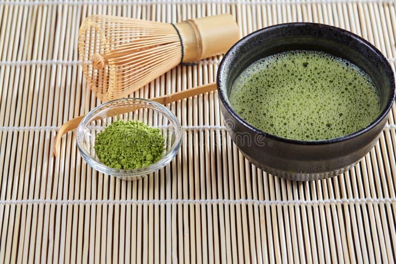 绿色matcha茶准备在一个竹碗碟衬垫设置了 免版税图库摄影