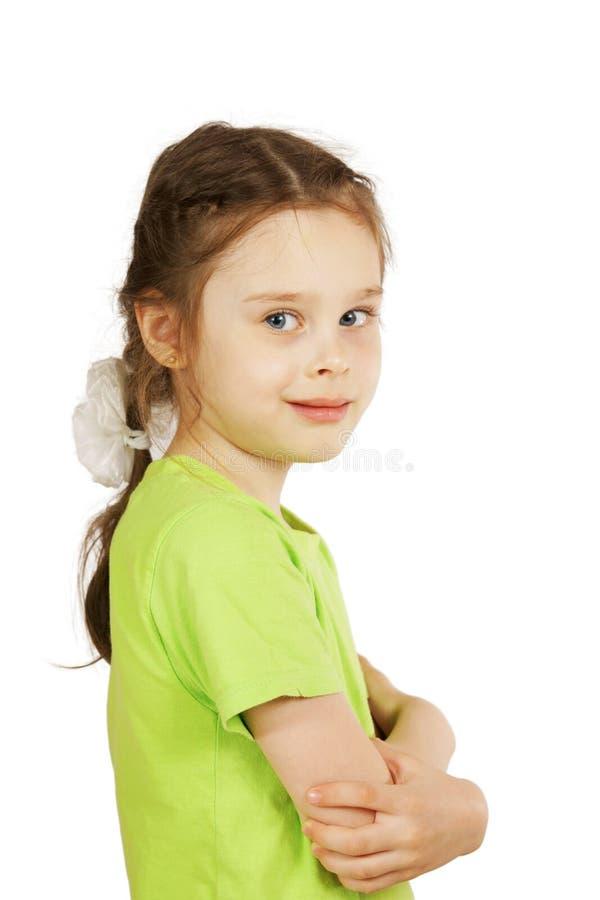 绿色T恤杉的小女孩站立斜向一边和微笑 免版税图库摄影