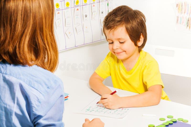 黄色T恤杉着色纸的男孩与铅笔 库存图片