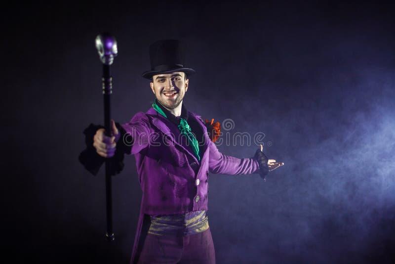 艺人 年轻男性艺人、赠送者或者演员阶段的 紫色女用短袖衬衣和圆筒的人 库存图片