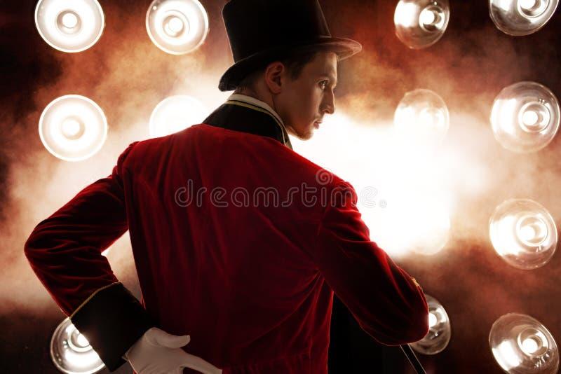 艺人 年轻男性艺人、赠送者或者演员阶段的 红色女用短袖衬衣和圆筒的人 库存图片