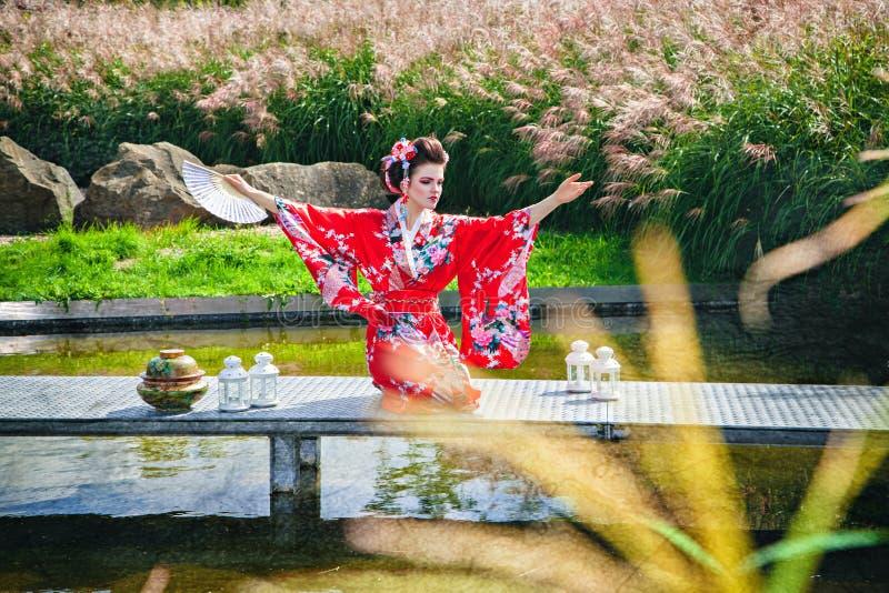 艺妓服装的妇女在桥梁的庭院里 免版税库存照片