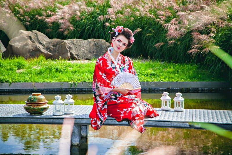 艺妓服装的微笑的妇女在庭院里 免版税库存照片