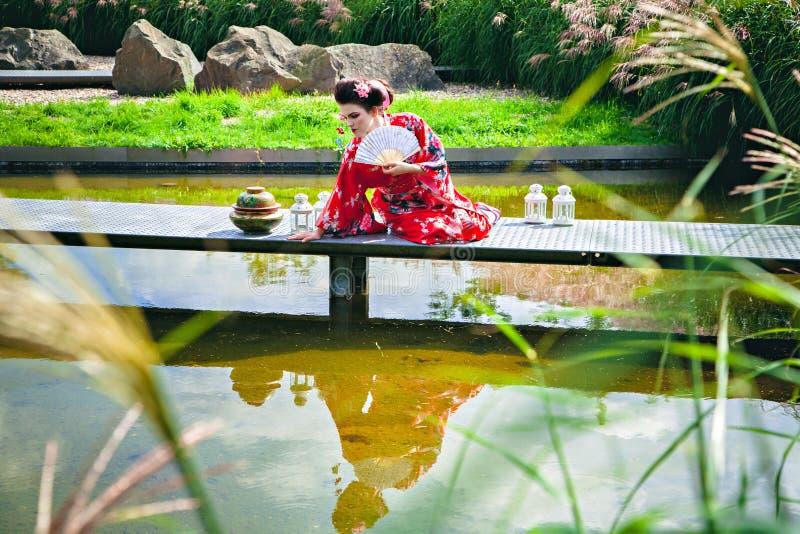 艺妓服装的美丽的妇女在桥梁的庭院里 免版税库存图片