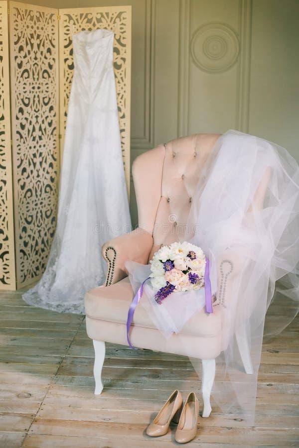 艺术与鞋带的婚礼礼服在木牡丹内阁折叠的屏幕花束在用软的布料柔和的淡色彩盖的桃红色椅子的 免版税库存照片