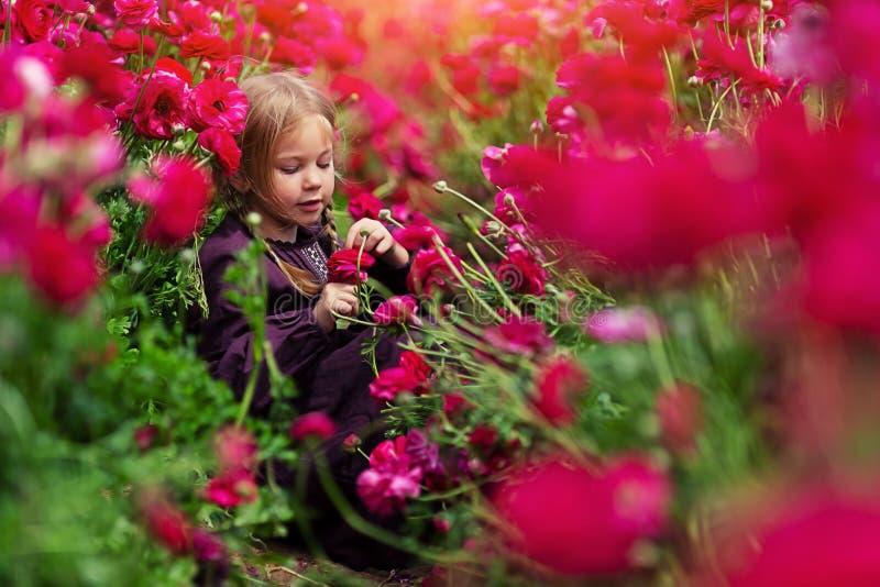 艺术修饰的照片 在明亮的花中的快乐的女孩 库存图片