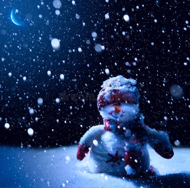 艺术圣诞夜-与雪人的背景在雪 图库摄影