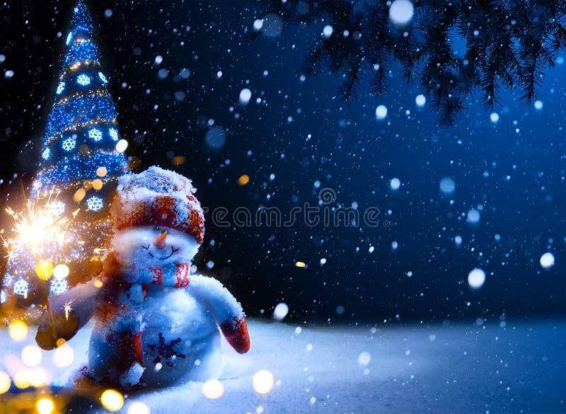 艺术圣诞夜-与雪人的背景在雪 免版税图库摄影