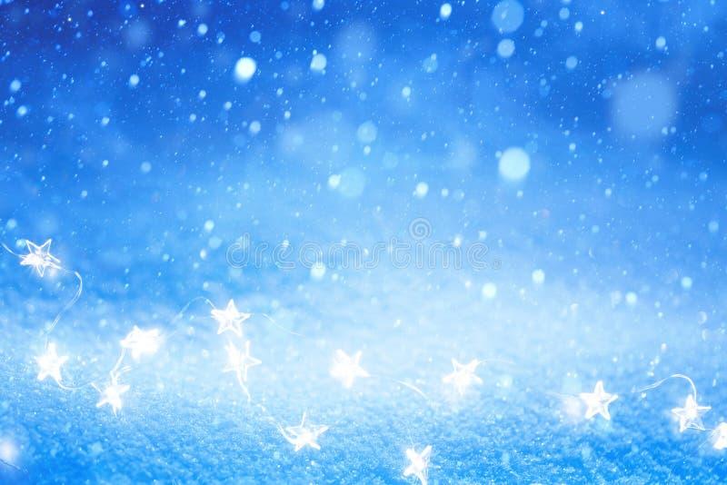 艺术在蓝色雪背景的圣诞灯 库存照片