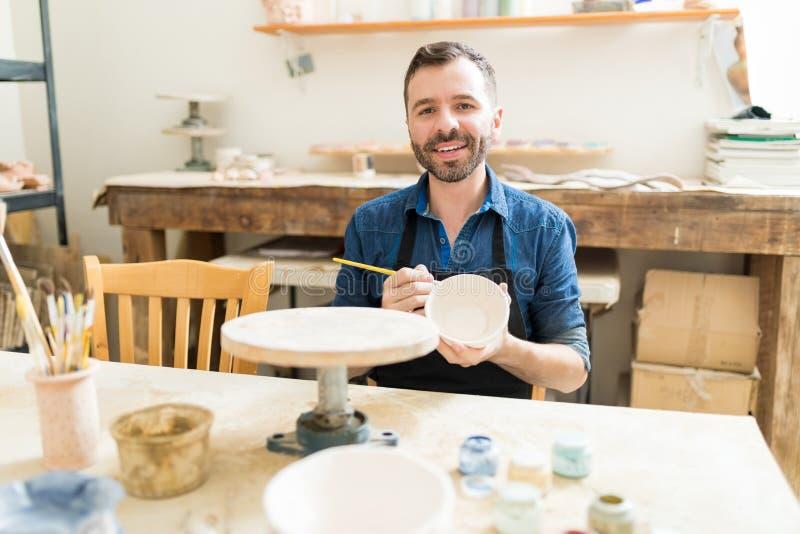 艺术家与油漆刷的绘画陶器在瓦器车间 库存照片