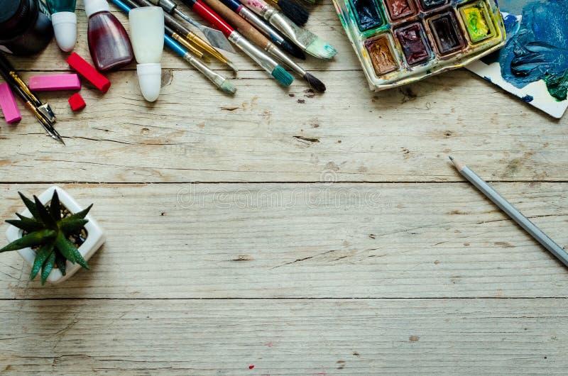 艺术家在木背景的画笔 免版税库存照片