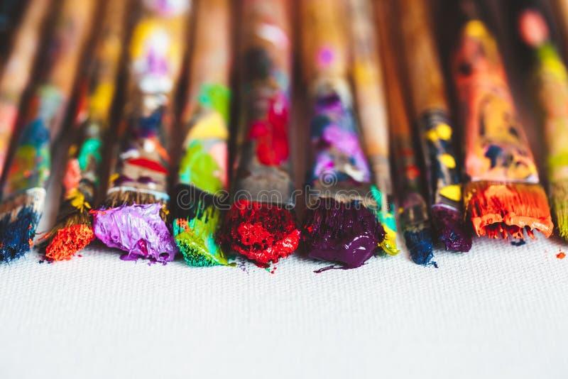 艺术家在艺术性的帆布的油漆刷特写镜头 免版税库存照片