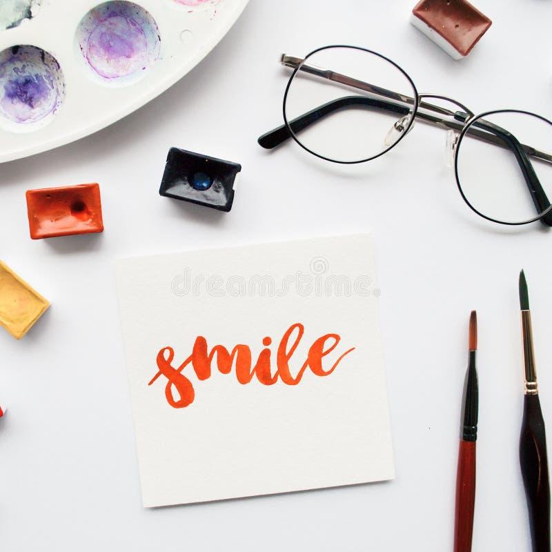 艺术家工作区 措辞在书法样式、水彩小试管和调色板写的微笑在白色背景 库存例证
