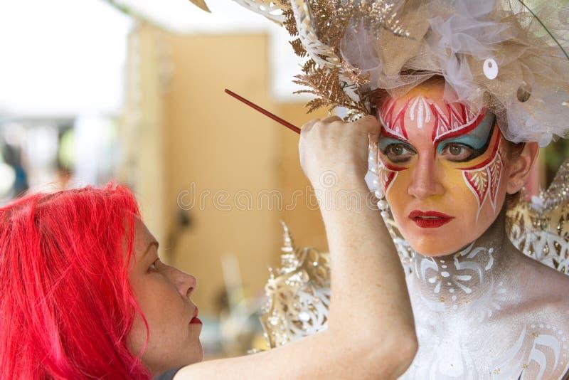艺术家应用人体彩绘于女性模型的面孔在节日 库存照片