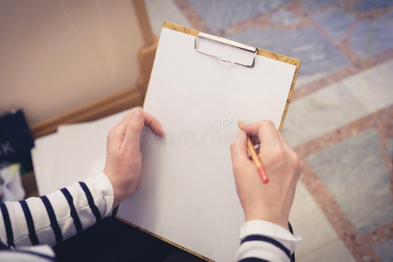 艺术家拿着画的一种片剂 免版税库存照片