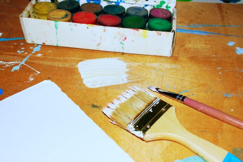 艺术家桌 木桌上的油漆、刷子和白纸 免版税库存图片