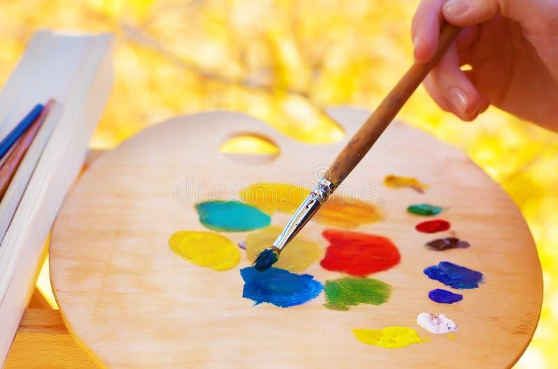 艺术家混合在调色板的油漆 免版税库存照片