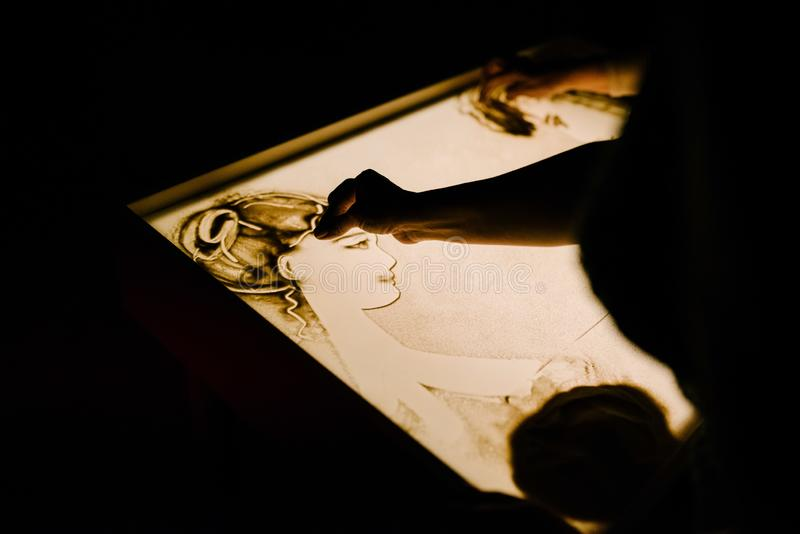 艺术家画沙子 在沙子的动画 库存图片