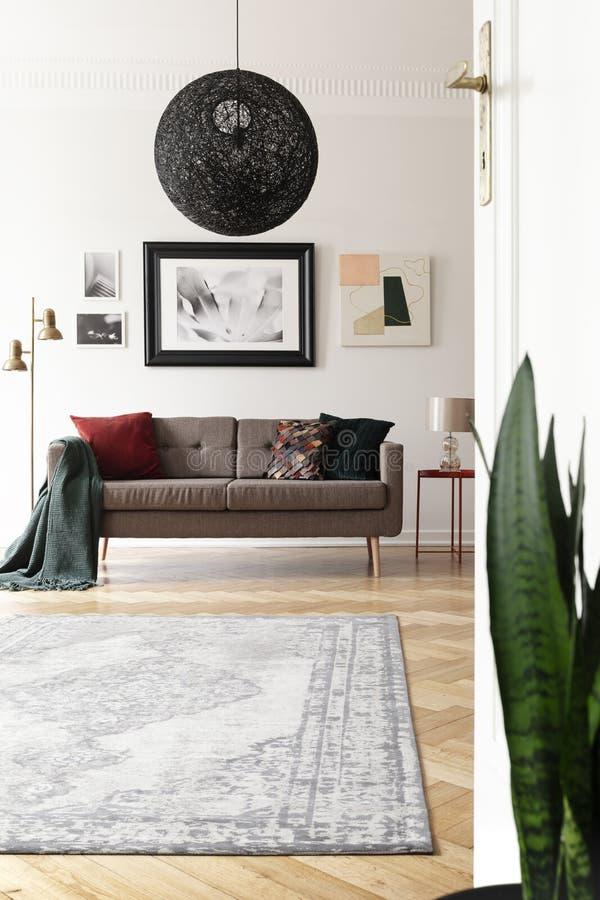 艺术性的客厅内部的低角度视图与大,黑,球状下垂光的在一个棕色沙发上 免版税库存图片