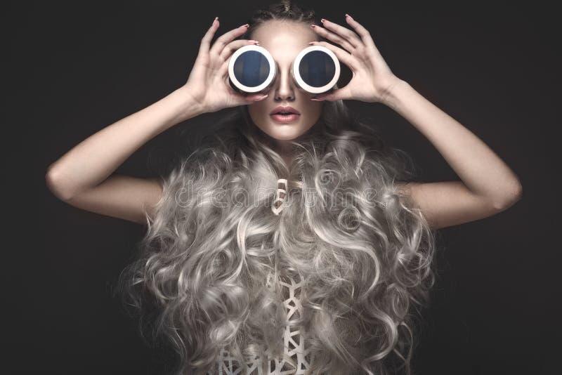 艺术礼服和先锋派发型的美丽的女孩与化妆产品在她的手上 秀丽表面 库存图片