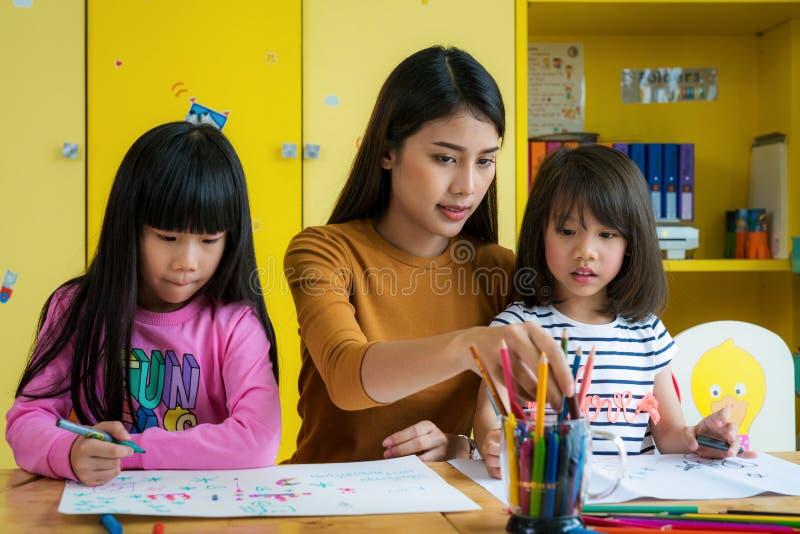 艺术课的亚裔老师和幼儿园学生 库存照片