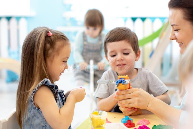 艺术课的孩子与老师在幼儿园 库存照片