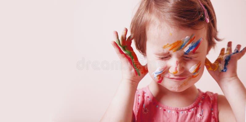 艺术,创造性和幸福童年概念 五颜六色的被绘的手和面孔在一个美丽的小孩女孩 免版税图库摄影