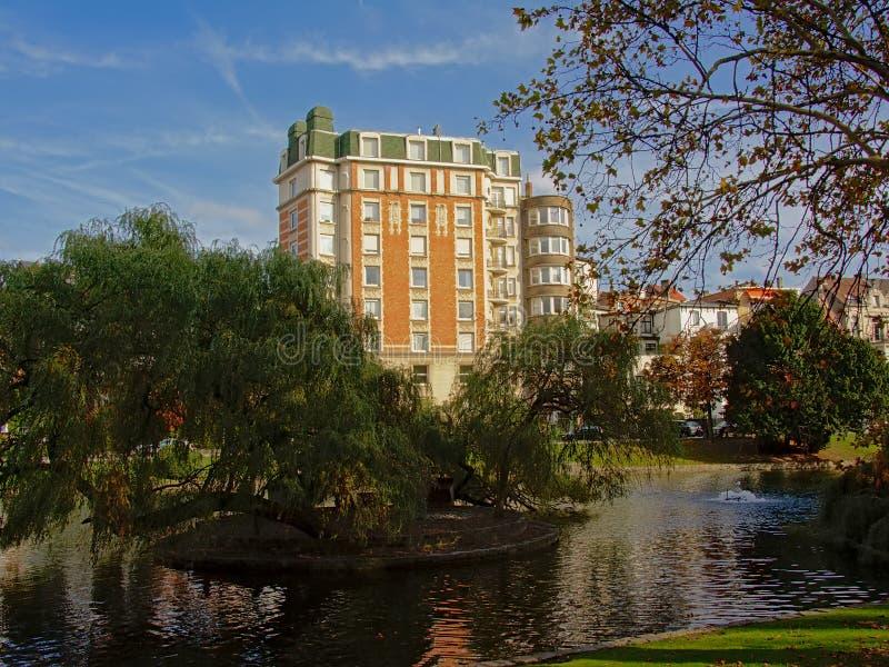 艺术nouveau公寓在Ixelles湖和桑特克鲁瓦教会的堤防的公园 免版税图库摄影