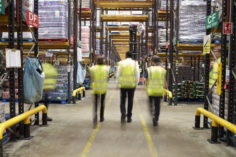 艾塞克斯,英国2016年3月13日:反射性背心的职员轻易地胜过照相机的在超级市场配给物仓库里 图库摄影